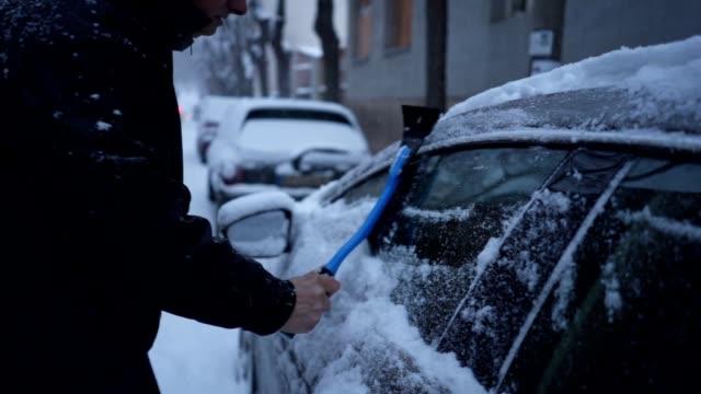 senior woman reinigung sein auto nach einem schneesturm - pavement stock-videos und b-roll-filmmaterial