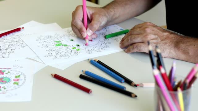 Senior Man Coloring a Coloring Sketch
