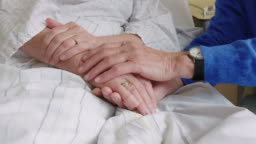Senior man comforting sick wife in hospital bed