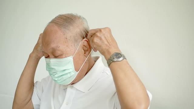 l'uomo anziano tossisce e indossa una maschera - apparato respiratorio video stock e b–roll