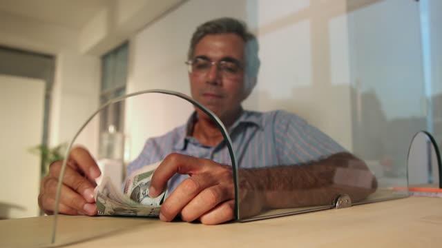 senior man counting money at bank counter, delhi, india - bank financial building stock videos and b-roll footage