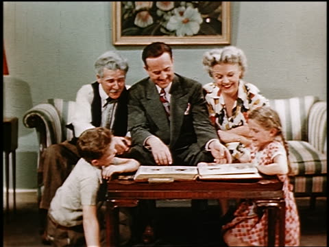 1946 senior man, couple + two children sitting on sofa + floor looking at photo album on table - 1946 stock videos & royalty-free footage