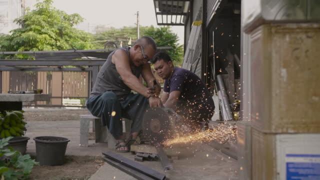 vídeos de stock e filmes b-roll de senior man cutting steel by cutting machine. - operário de linha de produção