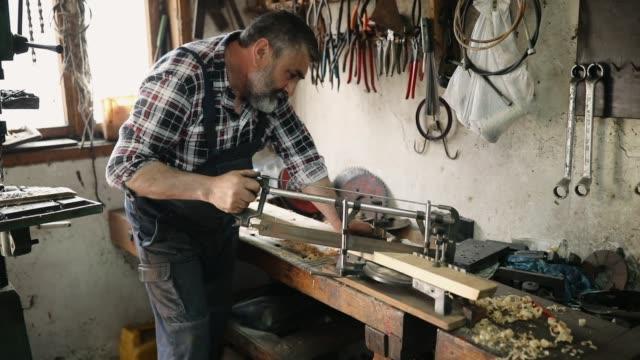 senior man cutting wood - pensionati lavoratori video stock e b–roll