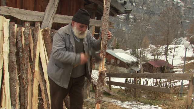 ms senior man cutting wood with hatchet / gimmelwald, berner oberland, switzerland - gimmelwald stock videos & royalty-free footage