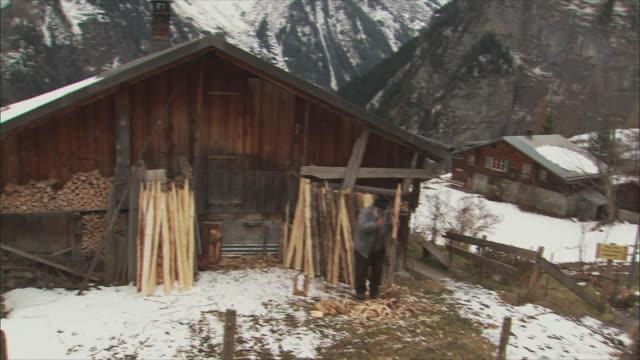 ws td tu senior man cutting wood with hatchet / gimmelwald, berner oberland, switzerland - gimmelwald stock videos & royalty-free footage