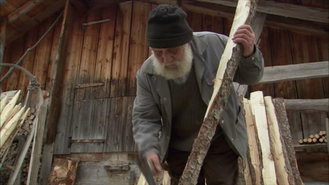 ms td senior man cutting wood with hatchet / gimmelwald, berner oberland, switzerland - gimmelwald stock videos & royalty-free footage