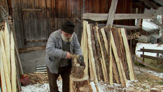 ms zo senior man cutting wood with hatchet / gimmelwald, berner oberland, switzerland - gimmelwald stock videos & royalty-free footage