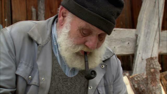 cu senior man cutting wood with hatchet / gimmelwald, berner oberland, switzerland - gimmelwald stock videos & royalty-free footage