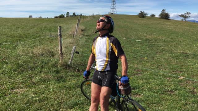 vídeos y material grabado en eventos de stock de senior man cycler tomando un descanso y disfrutando del paisaje - pasatiempos