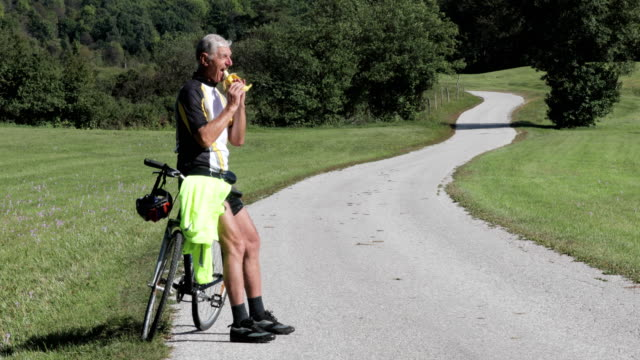 senior man cycler taking a break to eat on country road - banana stock videos & royalty-free footage