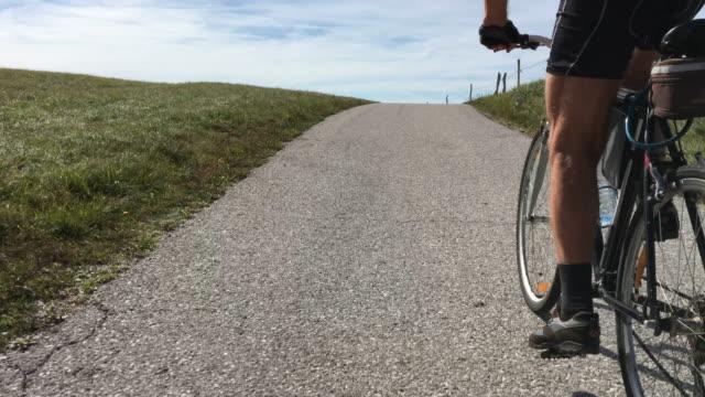vidéos et rushes de homme aîné faisant le vélo vers le haut - qui monte