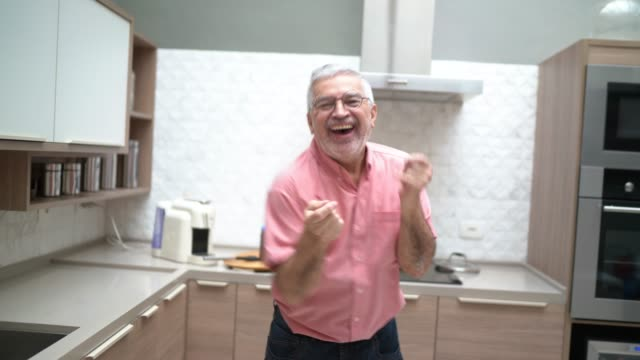 vídeos de stock e filmes b-roll de senior man dancing and cooking in the kitchen - bailarina