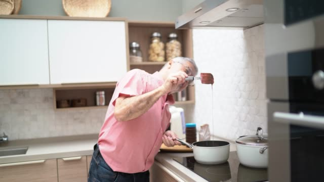 senior man dancing and cooking in the kitchen - 65 69 anni video stock e b–roll