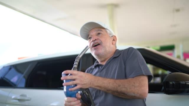 senior man dancing and singing at gas station - refueling stock videos & royalty-free footage
