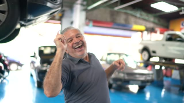 senior man dancing in auto repair - senior men stock videos & royalty-free footage