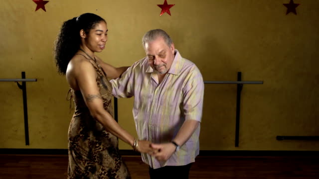 senior man dancing salsa with attractive woman - salsa stock videos & royalty-free footage