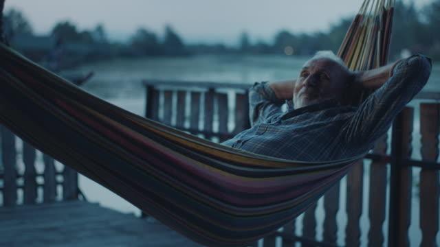 senior mann tagträumen in hängematte - vollbart stock-videos und b-roll-filmmaterial