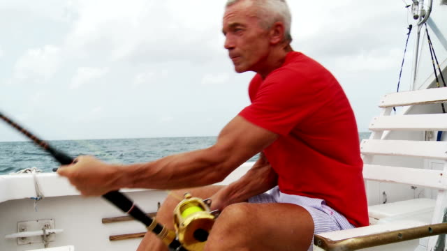 senior man deep sea fishing - fishing rod stock videos & royalty-free footage