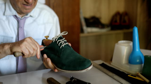 Senior man designing shoes in a small office