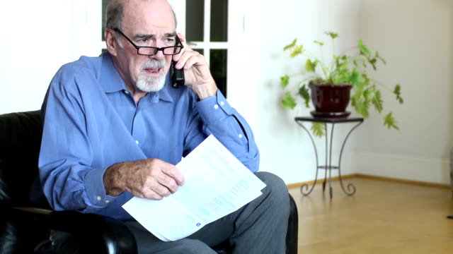 senior man discusses bills and documents over phone - one senior man only stock videos & royalty-free footage