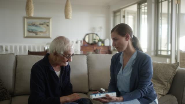vídeos de stock e filmes b-roll de senior man discussing with nurse over medicines - enfermeira