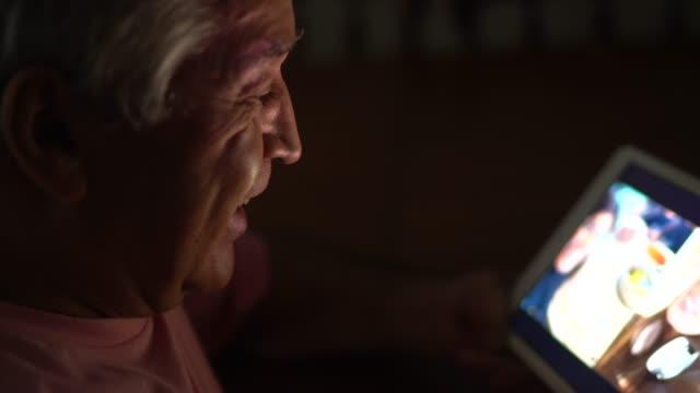 vídeos de stock, filmes e b-roll de idoso fazendo uma chamada de vídeo em tablet digital em casa - avô