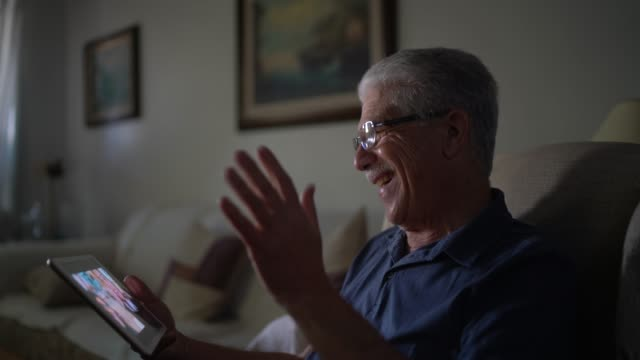 senior man doing a video call on digital tablet at home - grandfather stock videos & royalty-free footage