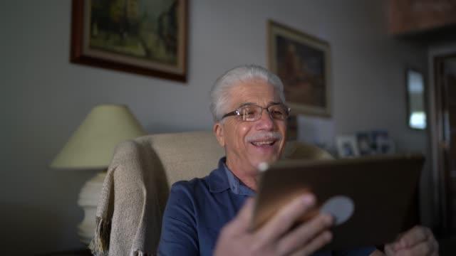 vídeos de stock, filmes e b-roll de idoso fazendo uma chamada de vídeo em tablet digital em casa - sentir a falta emoção