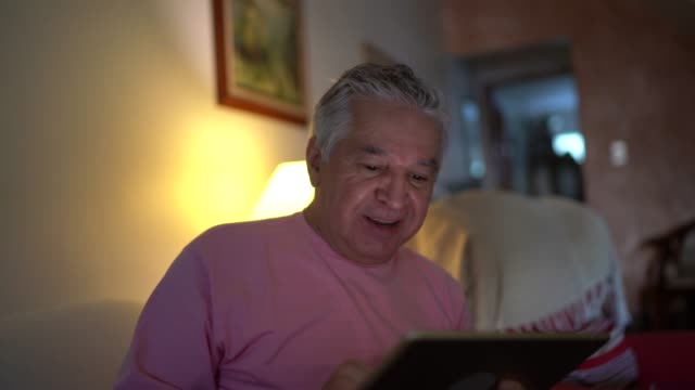 senior man doing a video call on digital tablet at home - long distance relationship stock videos & royalty-free footage