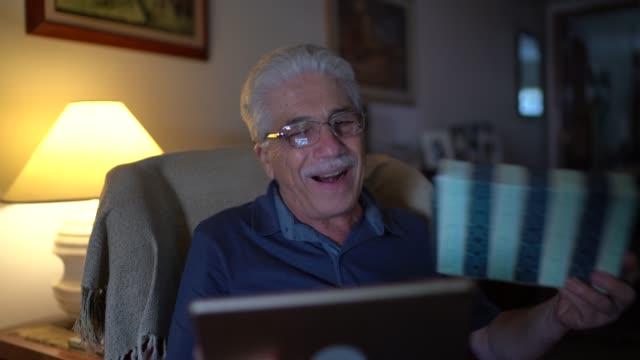 Homme aîné faisant un appel vidéo sur la tablette numérique à la maison