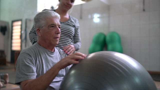 senior man doing physical therapy with ball - balance stock videos & royalty-free footage