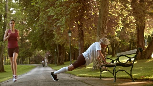 stockvideo's en b-roll-footage met ds senior man doen pushups op een bankje - oefeningen met lichaamsgewicht
