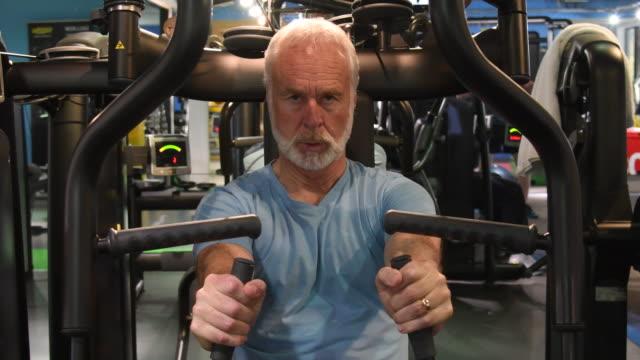 Senior man doing strength training on upper body exercise machine