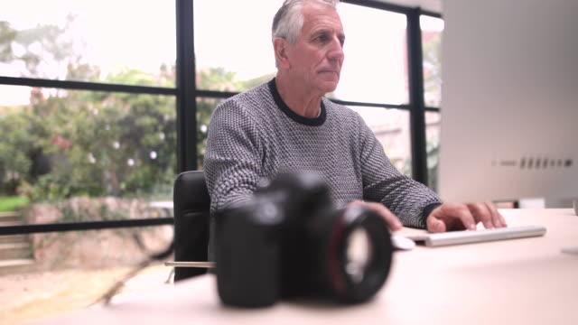 Senior man downloading photos to a computer
