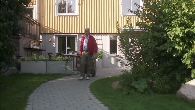 Senior man dragging a dustbin, Sweden.