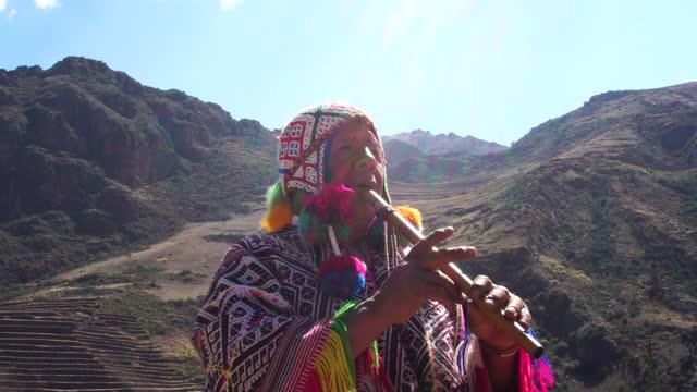 vídeos y material grabado en eventos de stock de hombre de la tercera edad vistiendo ropa tradicional peruana y tocando la flauta - culturas