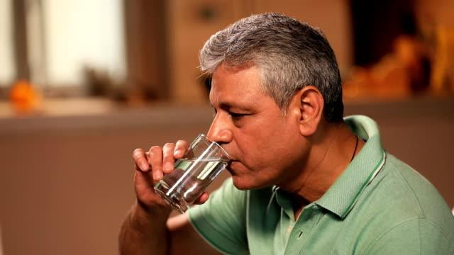 vídeos y material grabado en eventos de stock de senior man drinking a glass of water, delhi, india - camisa de polo