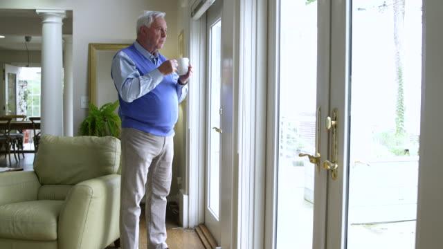 vídeos de stock e filmes b-roll de senior man drinking coffee and looking out of patio door - camisola sem manga