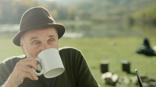 Senior man drinking coffee on camping trip by the lake