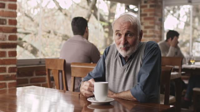 コーヒーを飲みながら老人男性