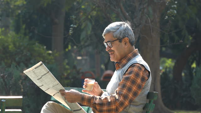 senior man drinking tea and reading newspaper at park bench - newspaper stock videos & royalty-free footage