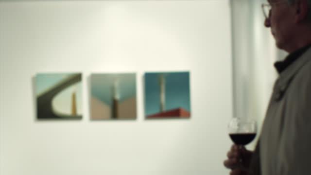 vídeos y material grabado en eventos de stock de ms r/f pan senior man drinking wine and looking at art in gallery / bilbao, vizcaya, spain. - museo de arte