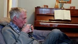 Senior man drinks tea in his living room side view