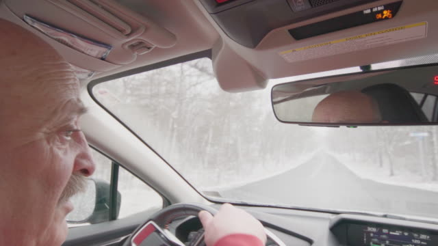 senior man driving a car under the snow - completely bald stock videos & royalty-free footage