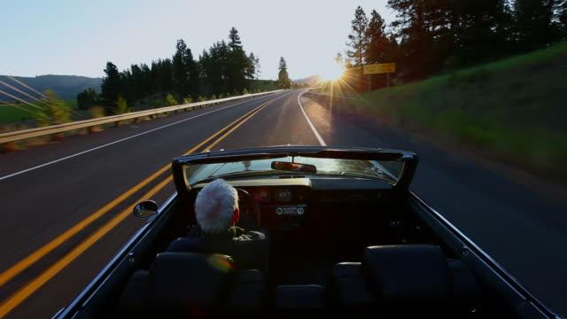 ws senior man driving convertible car at sunrise on rural road/washington, usa - old convertible stock videos & royalty-free footage