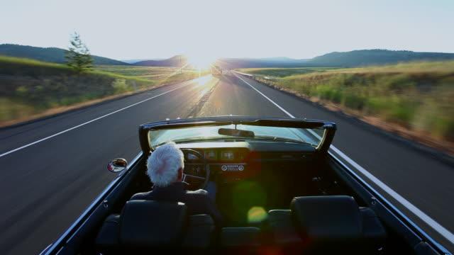 WS Senior man driving convertible car at sunrise on rural road/Washington, USA