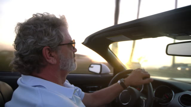 vídeos de stock, filmes e b-roll de senior man driving in a convertible along the beach - active seniors
