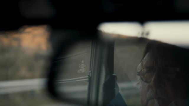 vídeos de stock e filmes b-roll de senior man driving reflected in rearview mirror - 70 anos