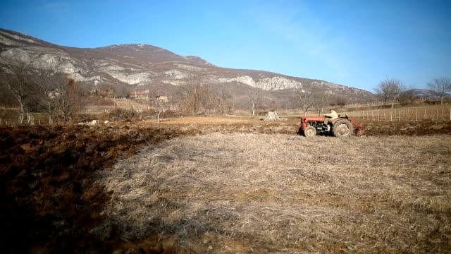 vidéos et rushes de homme aîné conduisant le petit tracteur et labourant l'activité de champ. agricultural. scène non urbaine - non urban scene